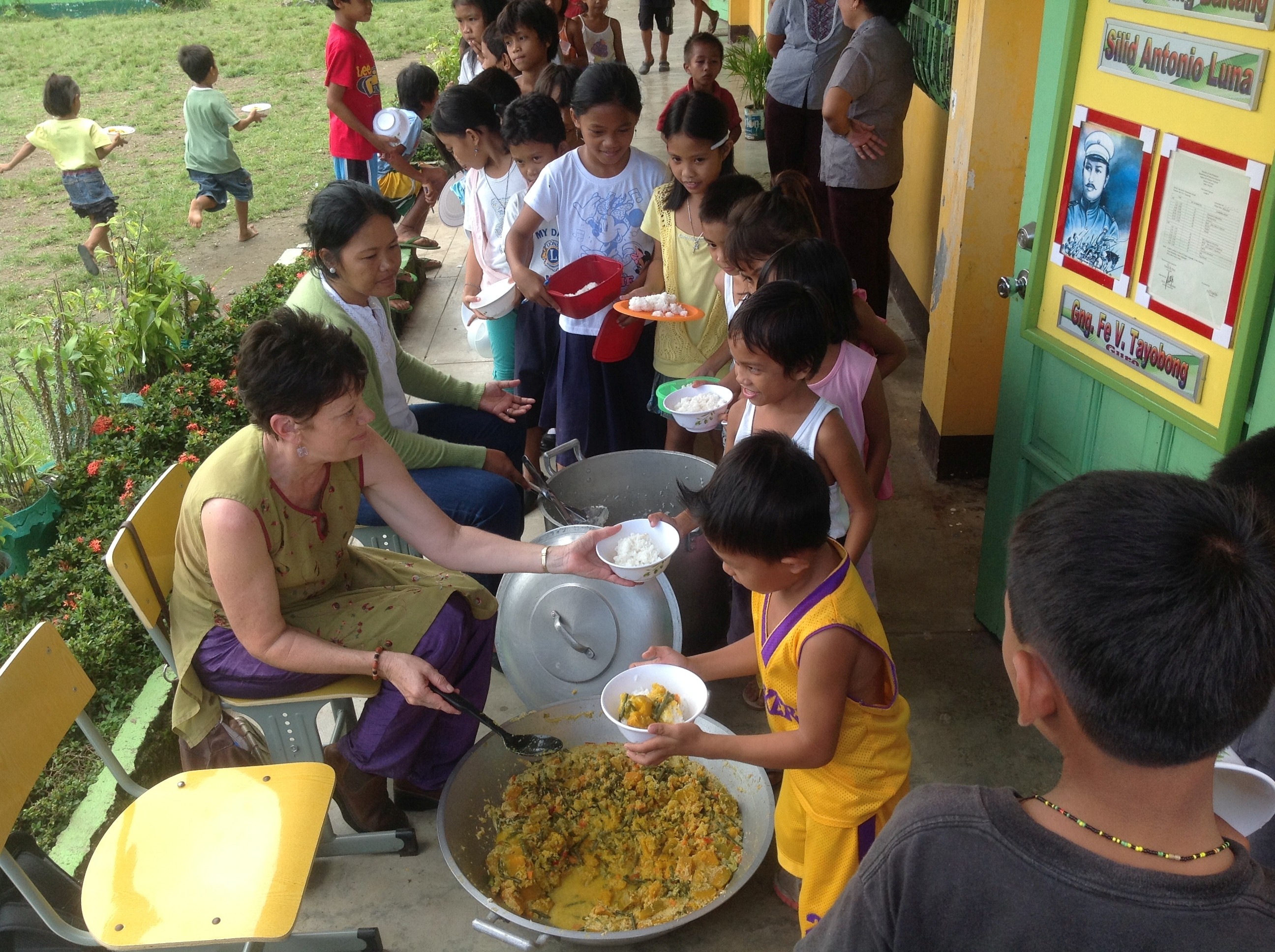 Sathya Sai Volunteers distributing food to children at School